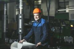 Het werken in productie tegen een achtergrond van machines van stock afbeelding