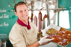 Het werken in slagerij met barbecuevlees Stock Afbeelding