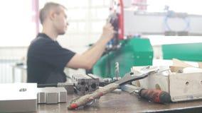 Het werken van instrumenten voor elektricien in overall is het werken met energiepaneel en machinesmateriaal aan stock video