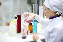 Het werkende laboratorium van de vrouw, de vaas van de glascilinder Royalty-vrije Stock Afbeeldingen