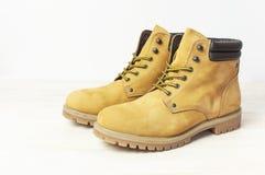 Het werklaarzen van gele mensen van natuurlijk nubuckleer op houten witte achtergrond In toevallige schoenen, de jeugdstijl Conce royalty-vrije stock afbeelding