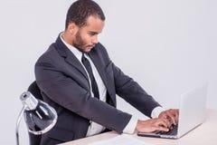 Het werklaptop Het glimlachen Afrikaanse zakenmanzitting bij de lijst Stock Fotografie