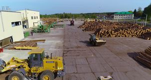 Het werkmateriaal in de yard van een houtbewerkingsfabriek, zware machines bij een zaagmolen stock footage