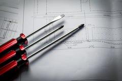 Het werkmateriaal van de close-up rood schroevedraaier met diagramdocument plan Royalty-vrije Stock Afbeelding