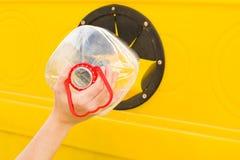 Het werpen van een fles in de recyclingscontainer Royalty-vrije Stock Afbeeldingen