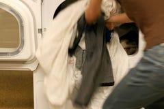 Het werpen van kleren in droger Stock Foto