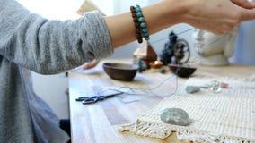 Het weven van parels Close-up die van vrouwen` s handen die parels op de draad vastbinden, juwelen in de workshop maken stock videobeelden