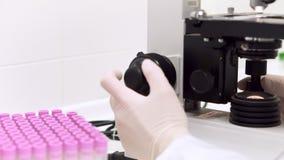 Het wiel dichte omhooggaand van de microscoopnadruk De artsen overhandigen het gebruiken van een microscoop om zich binnen op een stock video