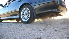 Het wiel van auto is misstap op een asfaltweg tijdens begin van beweging De kleine stenen en het vuil zijn vlieg uit van onder de stock videobeelden