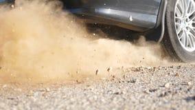 Het wiel van auto is misstap op een asfaltweg tijdens begin van beweging De kleine stenen en het vuil zijn vlieg uit van onder de stock footage