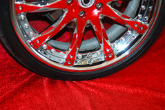 Het wiel van Chromeplated op een rood stock afbeeldingen