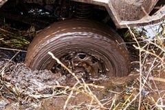 Het wiel van de auto glijdt in de modder in het moeras uit Stock Fotografie