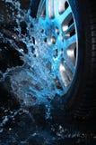 Het wiel van de auto met blauw water Stock Afbeelding