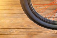 Het wiel van een modieuze fiets met een zwarte rand en een zwarte rubberband, rode spokes, een modieuze houten achtergrond stock foto's
