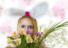 Het wijfje dat van de paashaas over bloemen kijkt Stock Foto