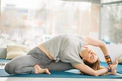 Het wijfje die van de Pilatestrainer uitrekkende oefening tonen stock foto's
