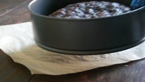 Het wijfje dient blauwe keukenhandschoen in neemt de vers gebakken eigengemaakte cake van de chocoladebrownie op de lijst stock videobeelden