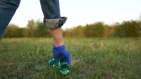Het wijfje dient een blauwe rubberhandschoen in opneemt een plastic fles van het gras Einde plastic concept, milieu stock videobeelden