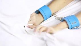 Het wijfje dient leerhandcuffs in Het speelgoed van het geslacht grijpt de witte bladen blauw leer en bont stock videobeelden