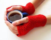 Het wijfje dient rode vuisthandschoenen in houdt een kop van hete drank royalty-vrije stock afbeeldingen