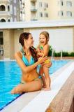Het wijfje en haar dochter hebben een pret dichtbij pool Stock Foto
