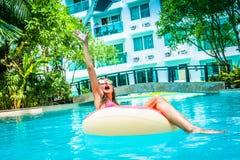 Het wijfje freelancer zit in een opblaasbare cirkel in de pool en werpt laptop in het water Bezig tijdens royalty-vrije stock afbeelding