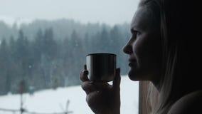Het wijfje heeft thee dichtbij een venster in de winter in toevlucht stock video