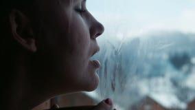 Het wijfje heeft thee en trekt hart op het venster stock footage