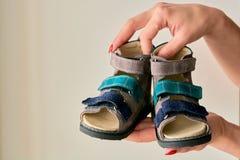 Het wijfje houdt close-up een orthopedische die de schoensandals van speciale kinderen van echt leer wordt gemaakt stock foto