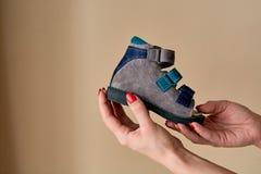 Het wijfje houdt close-up een orthopedische die de schoensandals van speciale kinderen van echt leer wordt gemaakt royalty-vrije stock afbeelding
