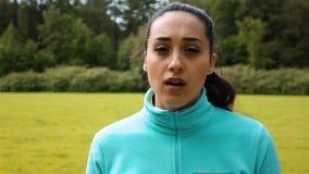 Het wijfje jogger kijkt buiten adem rond met een subtiele glimlach op haar gezicht in langzame motie, stock videobeelden