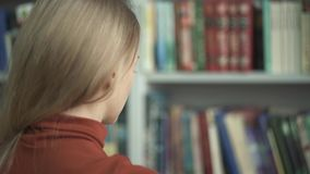 Het wijfje kiest welk boek in de bibliotheek te nemen stock video