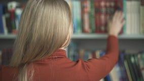 Het wijfje kiest welk boek in de bibliotheek te nemen stock footage