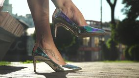 Het wijfje in modieuze zilveren schoenen op hoge hielen zit op een bank in park stock footage