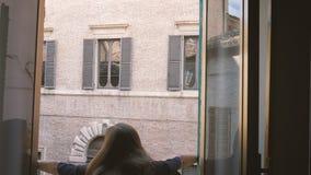 Het wijfje opent blinden van oud venster kijkend aan de straat van oude Italiaanse stad stock footage