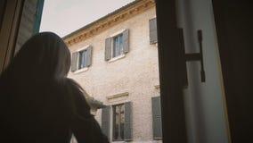 Het wijfje opent blinden van oud venster kijkend de straat oude Italiaanse stad stock footage