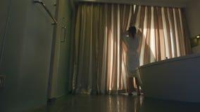 Het wijfje opent gordijnen op een venster stock footage