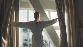 Het wijfje opent gordijnen op een venster stock video