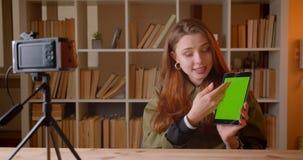 Het wijfje vlogger toont het groene chromascherm van tabet in videocamera op boekenrekkenachtergrond stock video