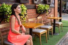Het wijfje wacht op iemand in een koffie op de straat van de vergadering, die haar hand golven aan een vriend, 4k royalty-vrije stock afbeeldingen