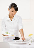 Het wijfje waiterss maakt vuile platen schoon Stock Foto's