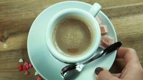 Het wijfje zet een kop van koffie op een lijst stock video