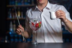 Het wijnglas met ijs, aardbeien en munt wordt gevuld doorbladert op de bedelaars die stock fotografie
