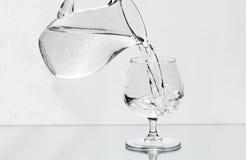 Het wijnglas wordt gevuld met een water van een kruik Royalty-vrije Stock Afbeeldingen