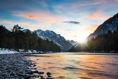 Het wijzen van op kleuren van zonsondergangwolken in landelijke rivier Stock Foto