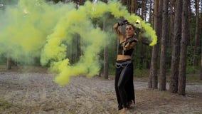 Het wilde kijken vrouw danst met brandstok en rookbom stock videobeelden