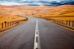 Het winden van zwarte asfaltweg door de zandduinen van Liwa-oase, Verenigde Arabische Emiraten royalty-vrije stock afbeeldingen