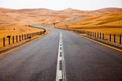 Het winden van zwarte asfaltweg door de zandduinen van Liwa-oase, Verenigde Arabische Emiraten stock afbeeldingen