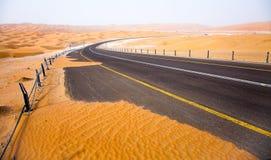 Het winden van zwarte asfaltweg door de zandduinen van Liwa-oase, Verenigde Arabische Emiraten stock foto's