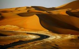 Het winden van zwarte asfaltweg door de zandduinen van Liwa-oase, Verenigde Arabische Emiraten royalty-vrije stock afbeelding